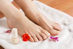 Schöne weibliche Füße mit Franzosen nagelt Pediküre auf weißem Tuch mit Blumen und Kerzen stockfotografie
