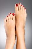 Schöne weibliche Füße mit roter Pediküre Lizenzfreie Stockfotografie
