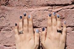 Schöne weibliche Hände mit außerordentlicher Maniküre auf einer Backsteinmauer Kreatives Nageldesign im Blau Ultra stilvolle Farb stockfoto