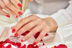 Schöne weibliche Hände mit Champagner Stockbild