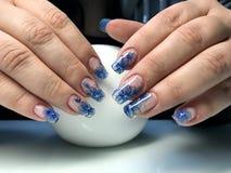 Schöne weibliche Hände mit einer transparenten Maniküre und einem modernen Design lizenzfreie abbildung