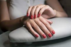 Schöne weibliche Hände mit roten Nägeln in der Schönheit nageln Salon Schöne weibliche Nägel und Maniküre lizenzfreies stockfoto