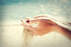 Schöne weibliche Hände und der Sand auf dem Seehintergrund Lizenzfreies Stockbild