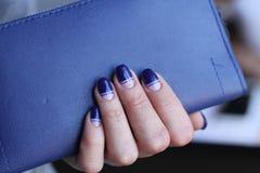 Schöne weibliche Hand mit Maniküre hält lederne Kupplung Dunkelblauer Nagellack mit kreativem Design stockfotografie