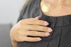 Schöne weibliche Hand mit Maniküre Ultra hellrosa Nagellack und Nagel entwerfen mit einem dünnen schwarzen Streifen stockfoto
