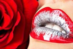 Schöne weibliche Lippen mit glänzendem Lippenstift und Rotrose Lizenzfreie Stockbilder