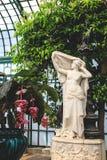 Schöne weibliche Statue in der bunten blühenden Orangerie Königliche Gewächshäuser von Laken in Belgien Stockfotografie
