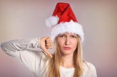 Schöne Weihnachtsfrau mit den Daumen unterzeichnen unten Lizenzfreie Stockbilder