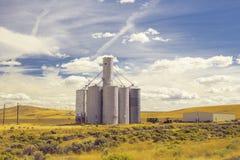 Schöne Weizenweidelandschaft und ein großer Silo rasen Türme an Stockbilder