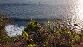 Schöne Wellen des Ozeans nähern sich felsigem Berg stock video footage