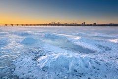 Schöne Winterlandschaft mit gefrorenem Fluss- und Sonnenunterganghimmel I Stockfotos