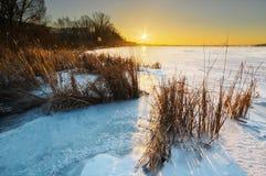 Schöne Winterlandschaft mit gefrorenem See- und Sonnenunterganghimmel Lizenzfreie Stockfotos