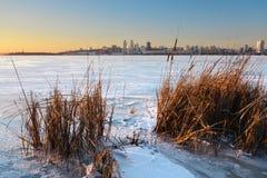 Schöne Winterlandschaft mit gefrorenem See- und Sonnenunterganghimmel Stockfoto