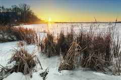 Schöne Winterlandschaft mit gefrorenem See- und Sonnenunterganghimmel Lizenzfreie Stockbilder