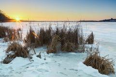 Schöne Winterlandschaft mit gefrorenem See- und Sonnenunterganghimmel Stockfotos