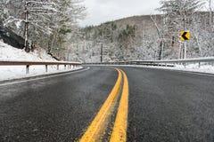 Schöne Winterlandschaft mit Landstraßenstraße mit Drehung und schneebedeckten Bäumen Stockbilder