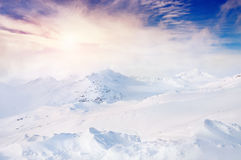 Schöne Winterlandschaft mit schneebedeckten Bergen bei Sonnenuntergang Lizenzfreie Stockfotos
