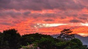 Schöne Wolke im roten und orange Himmel in der Dämmerung mit Berg, Bäumen und rotem Haus ` s Dach Stockbild