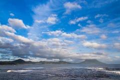 Schöne Wolken und Ozean mit Mt Kaimon in Kagoshima, Japan lizenzfreie stockbilder