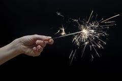 Schöne Wunderkerze in der Hand auf schwarzem Hintergrund Lizenzfreie Stockfotografie
