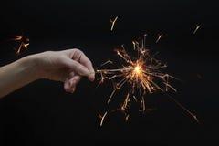 Schöne Wunderkerze in der Hand auf schwarzem Hintergrund Stockfotografie