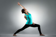 Schöne Yogadame, die im grauen Hintergrund steht Stockfoto