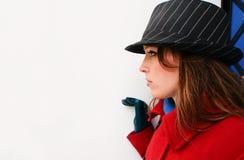 Schöne Yong-Frau im roten Mantel hinter der weißen Wand Stockfotografie