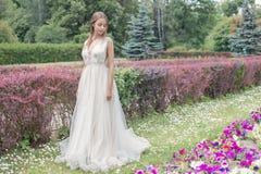 Schöne zarte Braut der jungen Frau in ihrer Hochzeitskleiderleichten Luft geht in den üppigen Garten an einem heißen sonnigen Som Stockfotografie