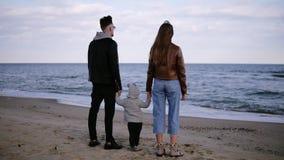 Schöne, Zeitlupeszene von jungem, Paaren mit ihrer Kinderstellung in der Front das Meer und an schauen umgearbeitet stock footage
