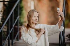 Schöne zufällige blonde stilvolle Modefrau mit einem Telefon in ihrer Hand machen selfie Europäische Gebäude und Straße auf einem Lizenzfreies Stockbild