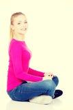 Schöne zufällige Frau, die auf dem Boden sitzt Stockbild