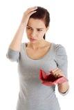 Schöne zufällige Frau mit der leeren Geldbörse, sorgend. Stockfotografie