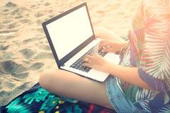 Schöne zufällige Frau mit einem Laptop auf dem Strand Stockfotos