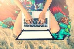 Schöne zufällige Frau mit einem Laptop auf dem Strand Lizenzfreie Stockfotos