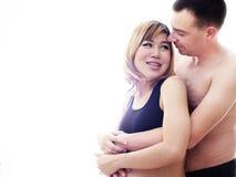 Schöne zukünftige Eltern: seine schwangere asiatische Frau und eine verantwortliche Umarmung des glücklichen Ehemanns zusammen Stockbild