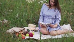 Schöne zukünftige Mutter, die das Buch auf dem Gebiet liest Sie nimmt Früchte stock footage