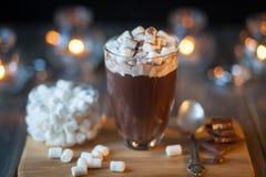 Schöne Zusammensetzung - heiße Schokolade mit Marmelade und Stücken in einem transparenten Glas Die Stände auf hölzernem Stand Lizenzfreie Stockfotos
