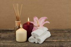 Schöne Zusammensetzung mit brennenden Kerzen, rosa Lilie und Badekurorttüchern auf hölzernem Hintergrund Stockfoto