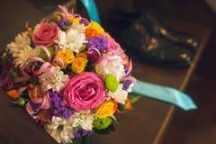 Schöne Zusammensetzung mit einem Blumenblumenstrauß und Hochzeitsschuhen Stockbilder