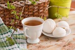 Schöne Zusammensetzung mit Tasse Tee und Eibisch Tasse Tee des Frühlings-Frühstücks A mit einem weißen Eibisch auf einem hölzerne Stockfoto