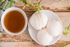 Schöne Zusammensetzung mit Tasse Tee und Eibisch Tasse Tee des Frühlings-Frühstücks A mit einem weißen Eibisch auf einem hölzerne Lizenzfreie Stockfotografie
