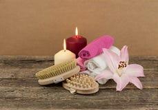 Schöne Zusammensetzung mit zwei Kerzen und Massagebürsten auf hölzernem Hintergrund Stockbilder