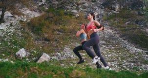 Schöne zwei Damen haben einen harten Trainingstag, der mitten in überraschender tragender Sportkleidung der Landschaftsgebirgsstr