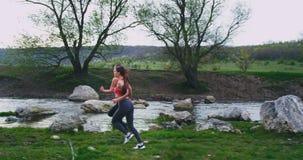 Schöne zwei Frauen mit, die den geeigneten Körpern stark laufen mitten in Gebirgsstraße mit überraschender Landschaft um Fluss si