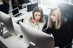Schöne zwei Geschäftsfrau, die in modernem lightfil Büro arbeitet Hübsche Mädchen an Arbeitsprozeß auf Tischrechner Lizenzfreies Stockfoto