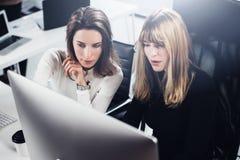 Schöne zwei Geschäftsfrau, die in modernem lightfil Büro arbeitet Hübsche Mädchen an Arbeitsprozeß auf Tischrechner Lizenzfreie Stockbilder