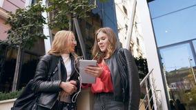 Schöne zwei Studentinnen unter Verwendung der lesenden guten Nachrichten des Tablet-Computers, Mittagspause mit Vergnügen an ausg stock video