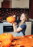 schönen Blondine malen Kürbise für Halloween zu Hause auf Küche stockfotografie