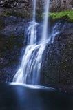 Schöner abgestufter Wasserfall, der über Felsen mit einem weichen ätherischen blauen Ton Refection im Wasser kaskadiert Lizenzfreie Stockfotos