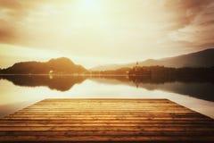 Schöner alpiner See mit der hölzernen Bank, geblutet, Slowenien, Weinlesebild Lizenzfreie Stockbilder